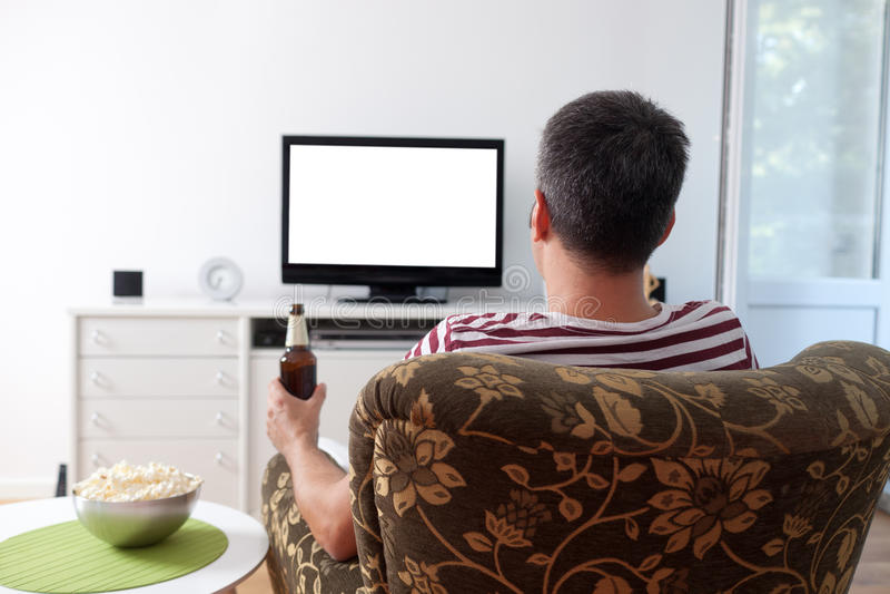 Hombre joven que ve la TV foto de archivo