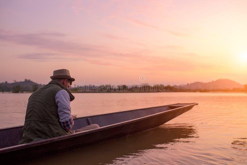 Hombre joven que viaja en barco el hora de la salida del sol foto de archivo