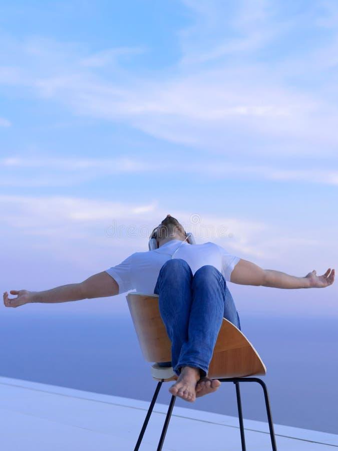 Hombre joven relajado en casa en balcón imagenes de archivo