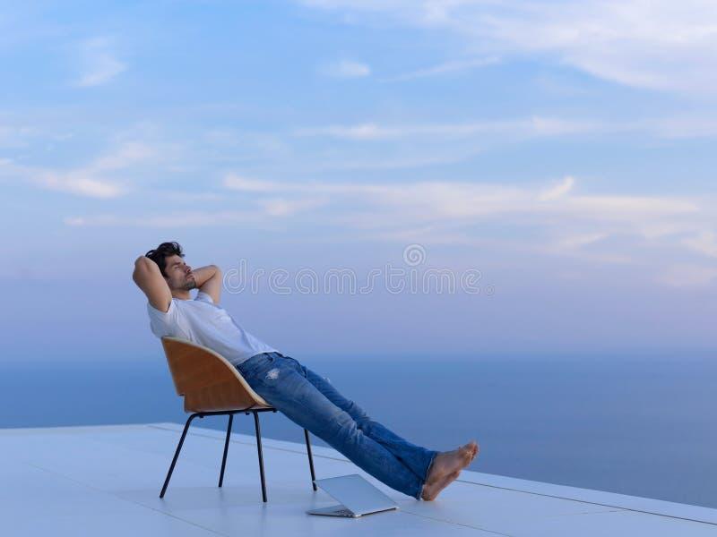 Hombre joven relajado en casa en balcón fotografía de archivo