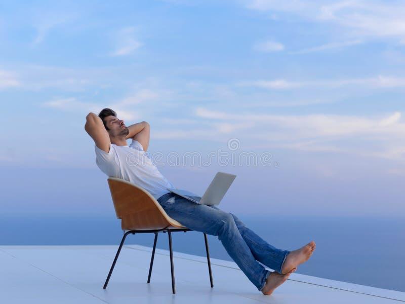 Hombre joven relajado en casa en balcón imágenes de archivo libres de regalías