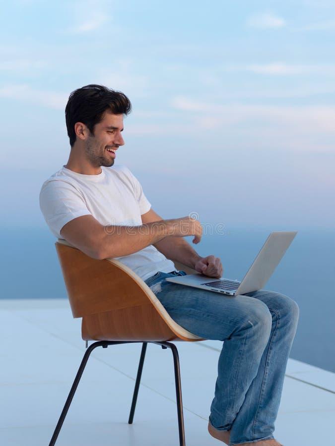 Hombre joven relajado en casa en balcón imagen de archivo libre de regalías