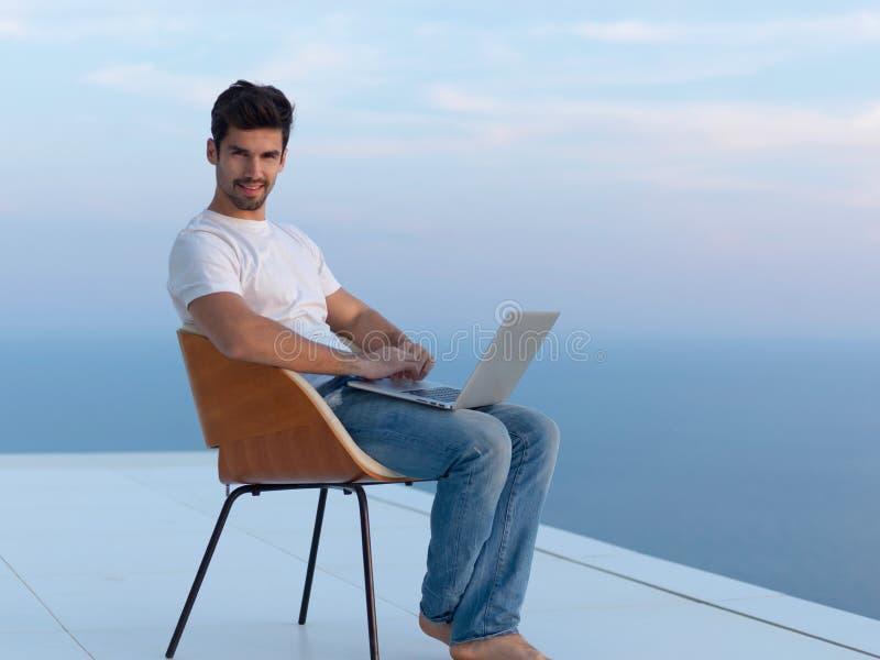 Hombre joven relajado en casa en balcón foto de archivo