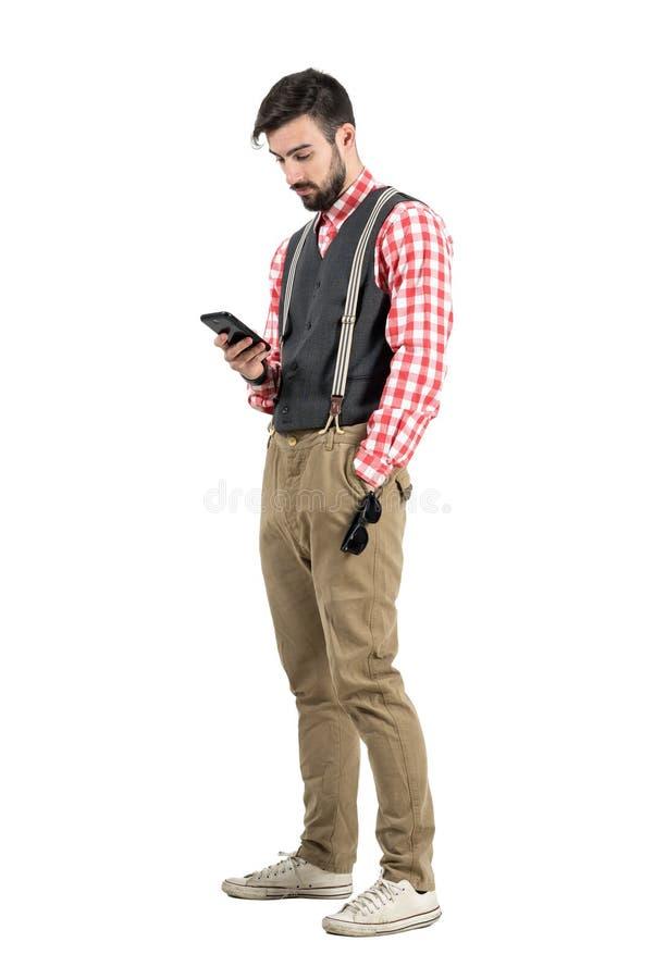 Hombre joven relajado en ropa retra que mecanografía el mensaje en smartphone imagenes de archivo
