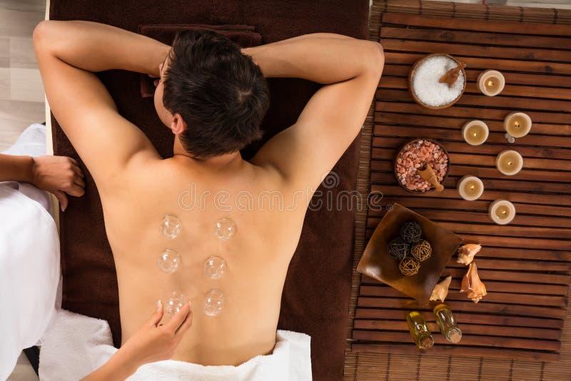 Hombre joven relajado que recibe la parte posterior de ahuecamiento del tratamiento encendido fotografía de archivo libre de regalías