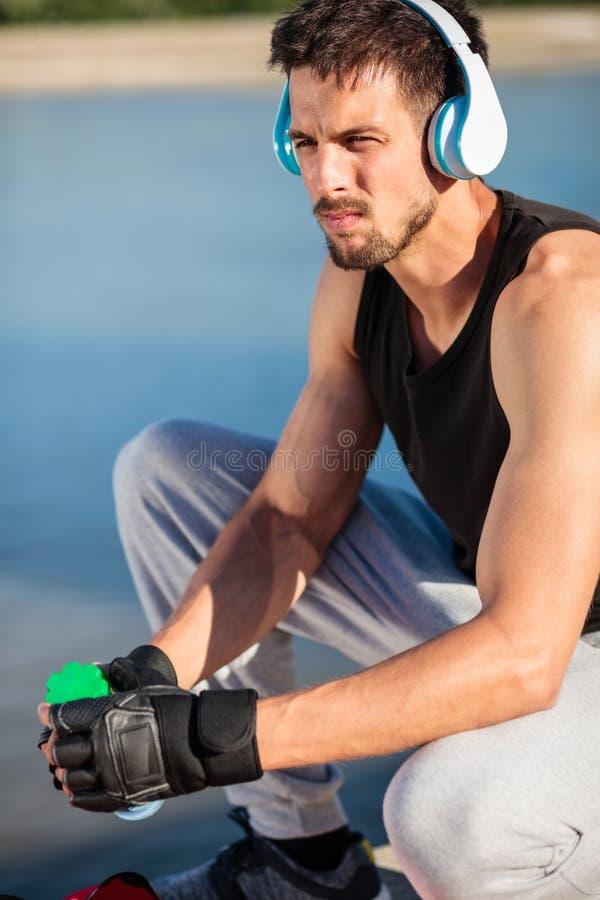 Hombre joven resuelto que escucha la música y que sostiene la botella de agua después del entrenamiento imagen de archivo