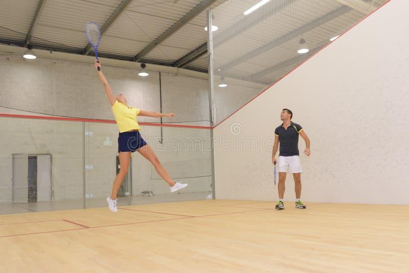 Hombre joven resuelto y mujer que juegan al tenis interior fotografía de archivo libre de regalías