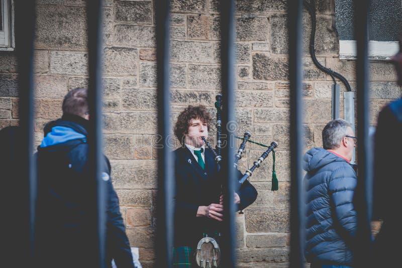 Hombre joven revestido en un tartán escocés tradicional que toca la gaita escocesa imagen de archivo