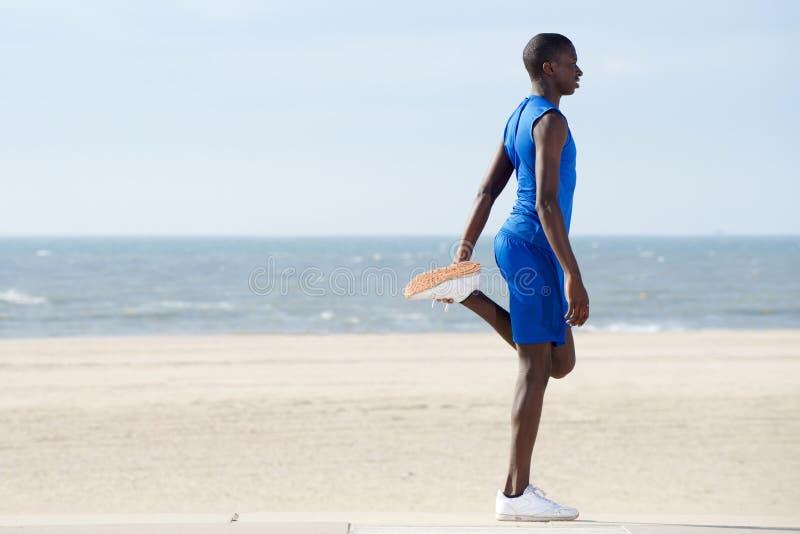 Hombre joven sano que ejercita en la playa foto de archivo