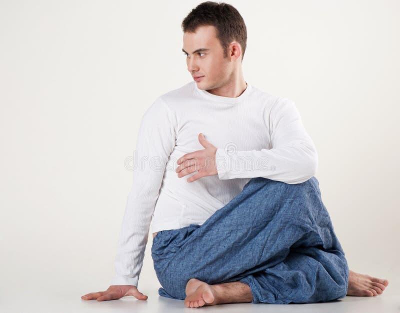 Hombre joven sano que hace yoga. Espina dorsal que tuerce actitud foto de archivo libre de regalías