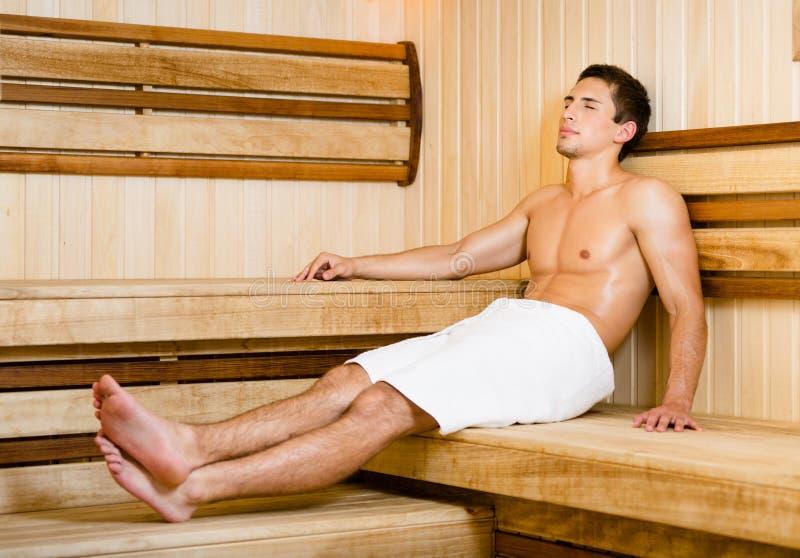 Hombre joven semidesnudo que se relaja en sauna imagenes de archivo