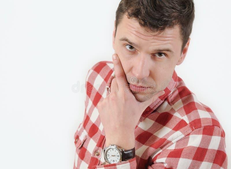 Hombre joven serio en la camisa del inconformista que lleva a cabo la mano en la barbilla y la situación contra el fondo blanco imagenes de archivo
