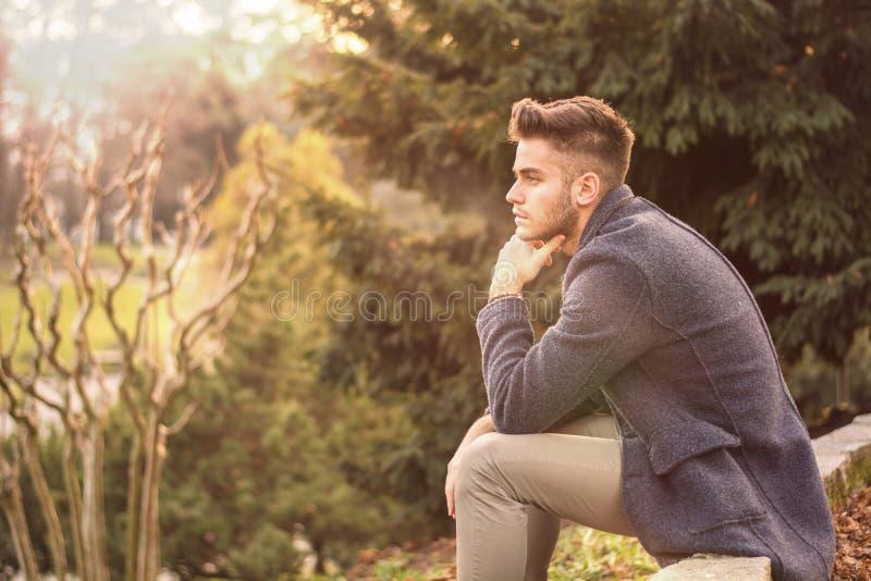 Hombre joven serio hermoso al aire libre que piensa foto de archivo
