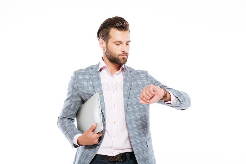Hombre joven serio que sostiene el ordenador portátil que mira el reloj imágenes de archivo libres de regalías