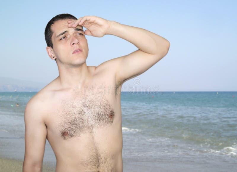 Hombre joven sin la camisa que mira lejos sobre fondo de la playa del verano foto de archivo libre de regalías