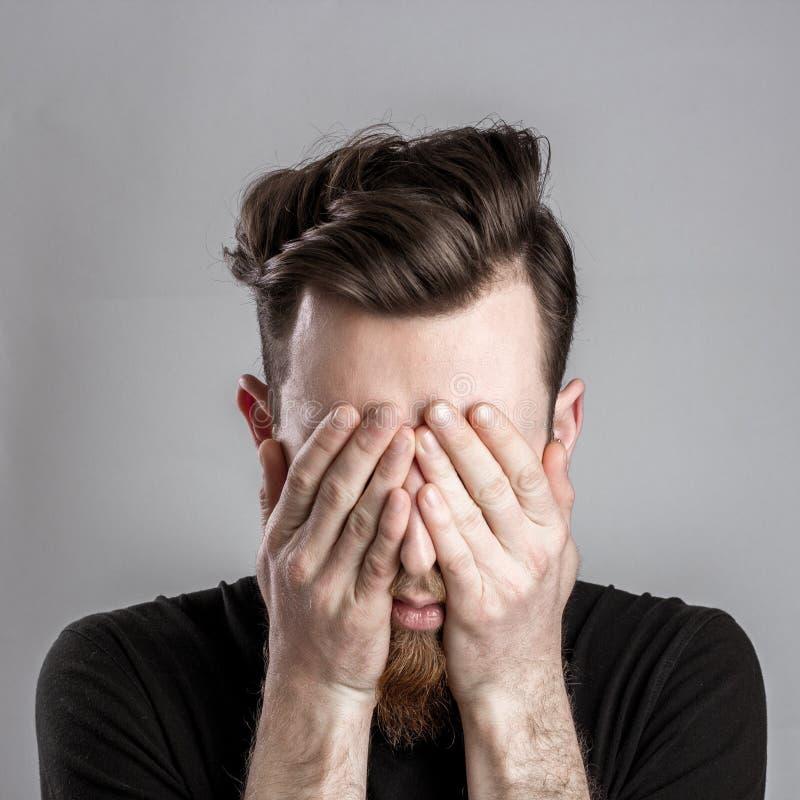 Hombre joven soñoliento cansado aislado en fondo gris imagenes de archivo