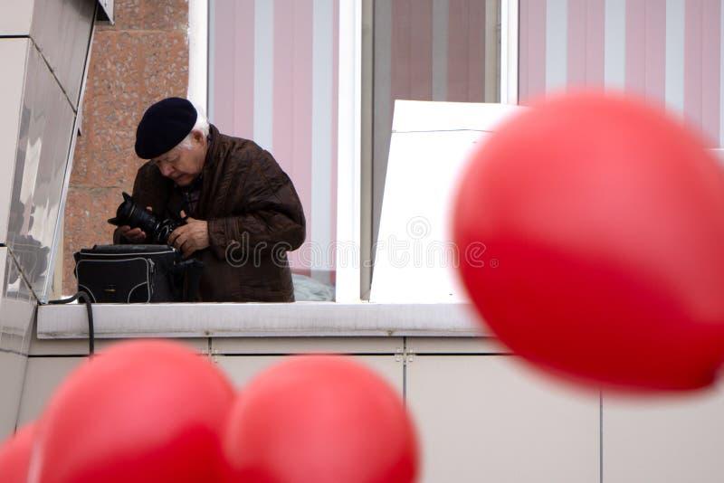 Hombre joven sobre la pared azul aislada que sostiene una cámara - Rusia Berezniki puede 9, 2018 imagen de archivo
