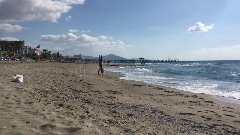 Hombre joven somersaulting en la playa cerca del mar almacen de video