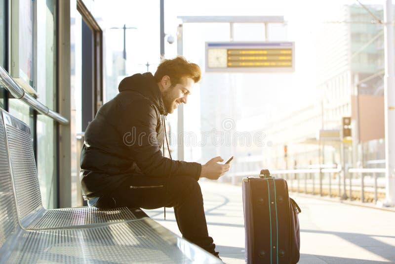 Hombre joven sonriente con el teléfono móvil y el bolso imágenes de archivo libres de regalías