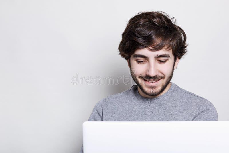 Hombre joven sonriente con la barba de moda y peinado que hace la llamada video con los amigos que están felices y contentos de h fotos de archivo libres de regalías