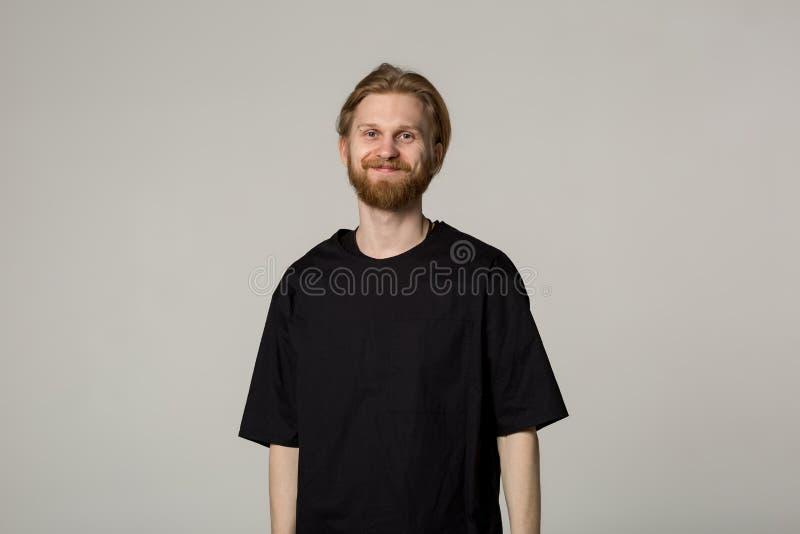 Hombre joven sonriente con la barba en camisa negra imagen de archivo libre de regalías