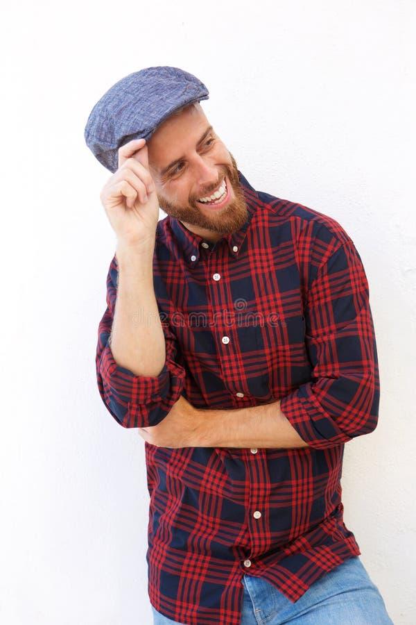 Hombre joven sonriente con la barba y sombrero que presenta contra el fondo blanco foto de archivo libre de regalías