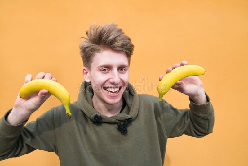 Hombre joven sonriente con los plátanos en sus manos en un fondo anaranjado Una mirada en la cámara foto de archivo libre de regalías