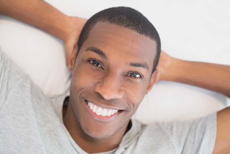 Hombre joven sonriente del Afro que descansa en cama imagen de archivo libre de regalías