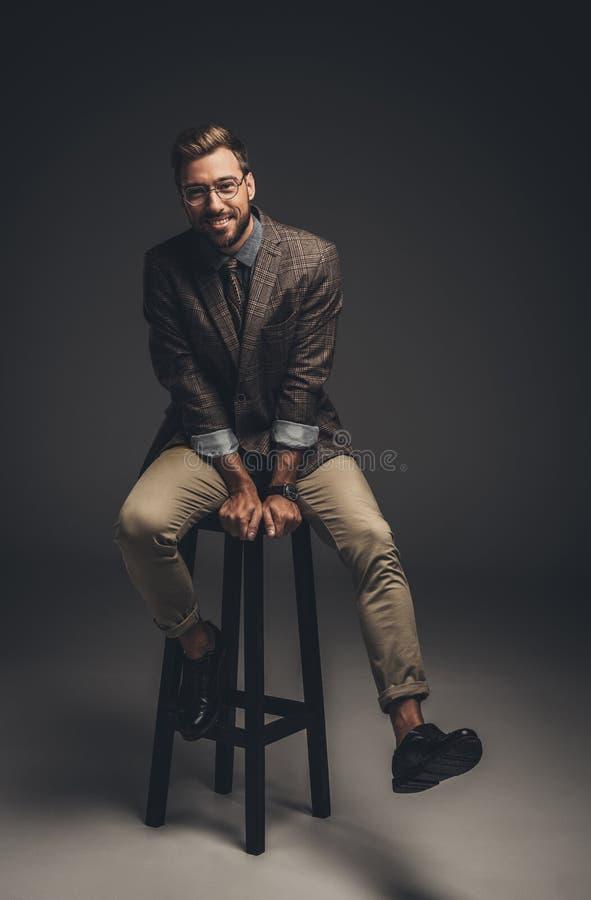 Hombre joven sonriente en el traje y los vidrios que se sientan en taburete de bar y la mirada imagen de archivo libre de regalías