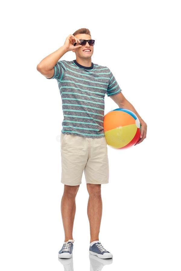 Hombre joven sonriente en gafas de sol con la pelota de playa imagenes de archivo