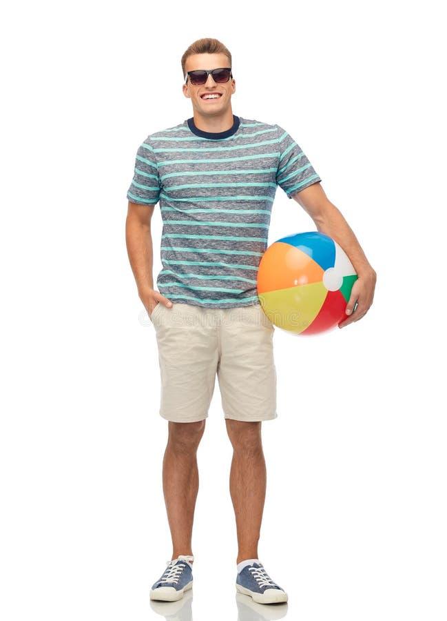 Hombre joven sonriente en gafas de sol con la pelota de playa fotos de archivo