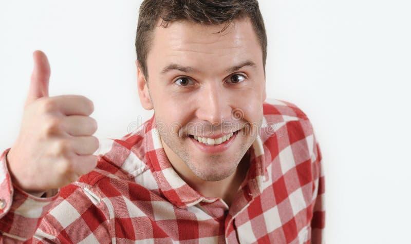 Hombre joven sonriente en la camisa del inconformista que muestra el pulgar para arriba y que se opone al fondo blanco fotos de archivo