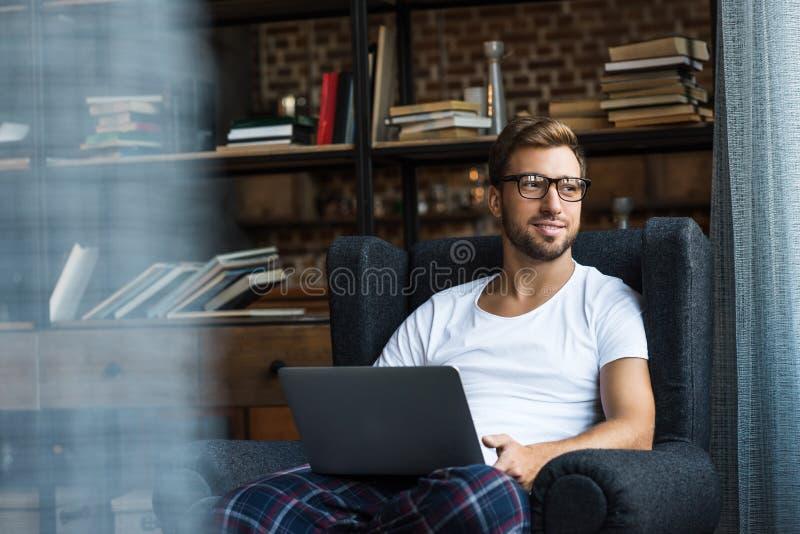 Hombre joven sonriente en la ropa casera y los vidrios, sentándose en butaca imagenes de archivo