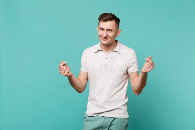 Hombre joven sonriente en la ropa casual que frota los fingeres, mostrando el gesto del efectivo, pidiendo el dinero aislado en l fotografía de archivo libre de regalías