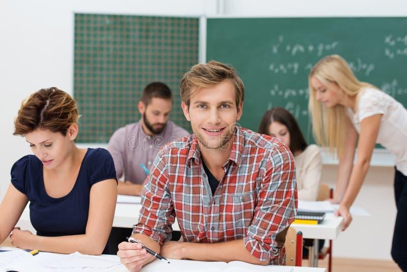 Hombre joven sonriente en la universidad o la universidad fotografía de archivo libre de regalías