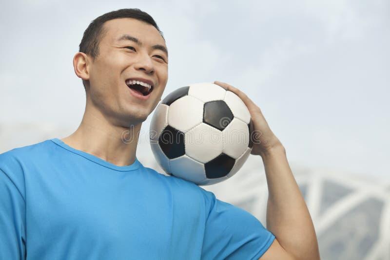 Hombre joven sonriente en una camiseta azul que sostiene el balón de fútbol en su hombro, al aire libre en Pekín, China foto de archivo