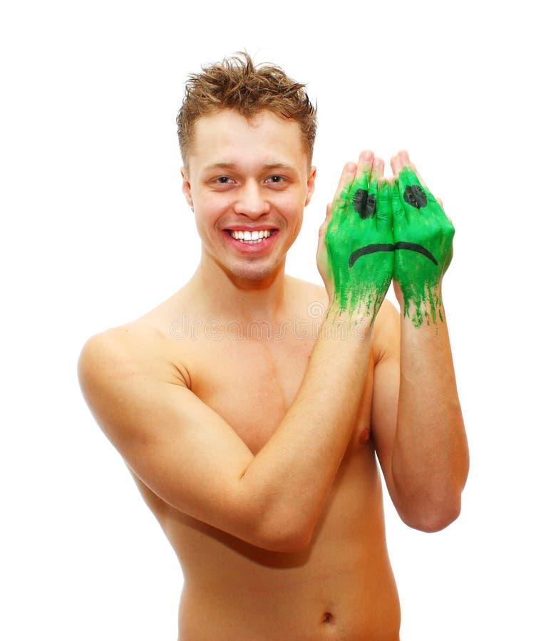 Hombre joven sonriente feliz con la pintura triste de la máscara de la sonrisa imagen de archivo libre de regalías