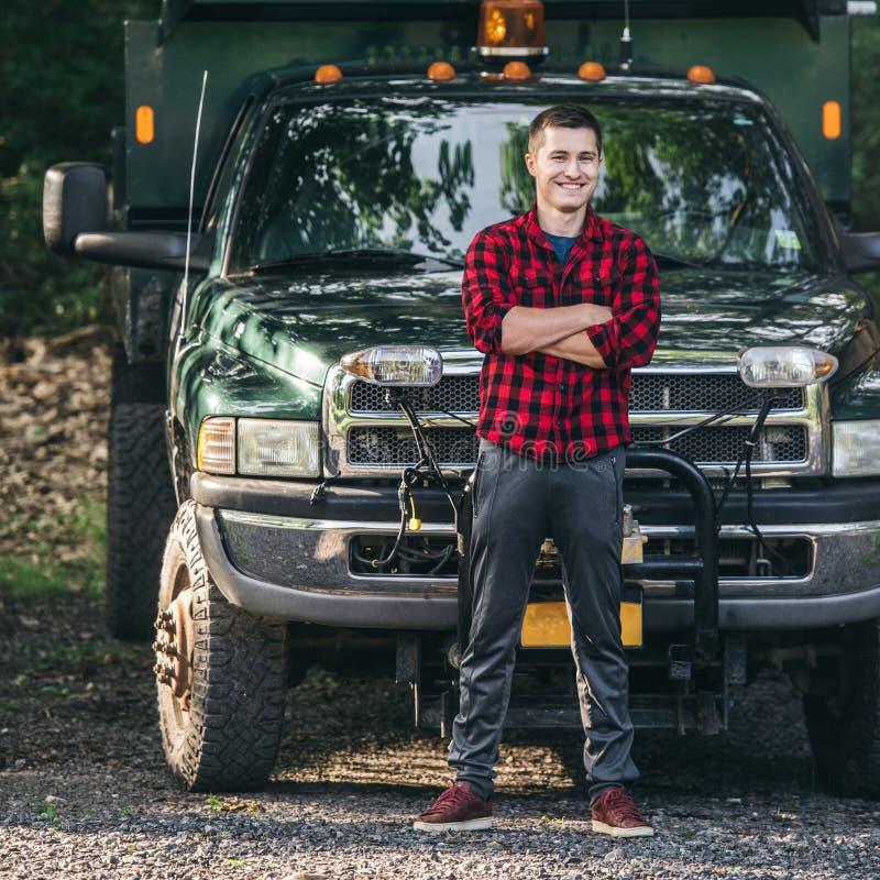 Hombre joven sonriente feliz del granjero que se coloca delante de la camioneta pickup lista para trabajar imagen de archivo