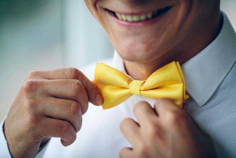 Hombre joven sonriente feliz en un traje de la boda y una mariposa amarilla foto de archivo libre de regalías