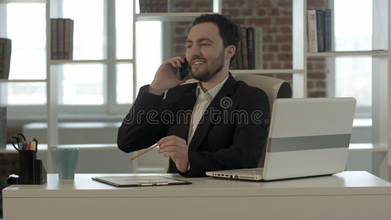 Hombre joven sonriente feliz que habla en el teléfono móvil en oficina foto de archivo libre de regalías