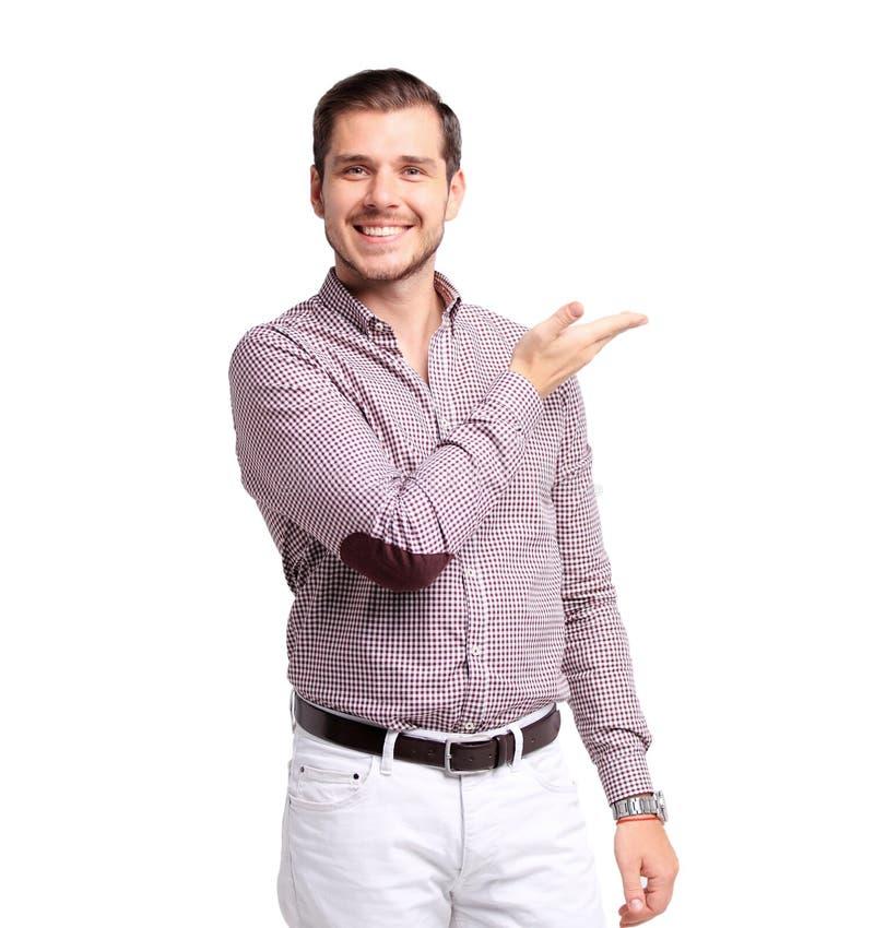 Hombre joven sonriente feliz que presenta y que muestra su texto o producto aislado en blanco imagenes de archivo