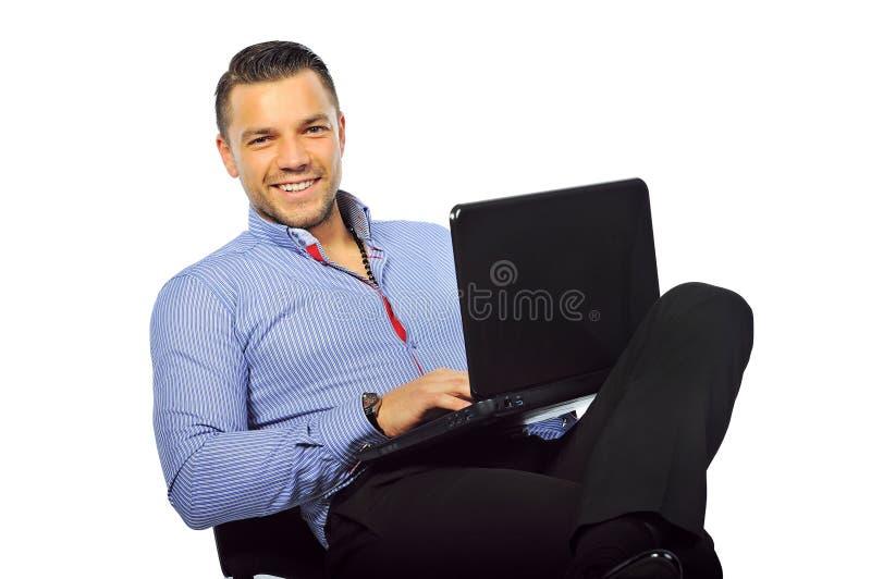 Hombre joven sonriente feliz que se sienta en el estudio con el ordenador portátil i foto de archivo libre de regalías