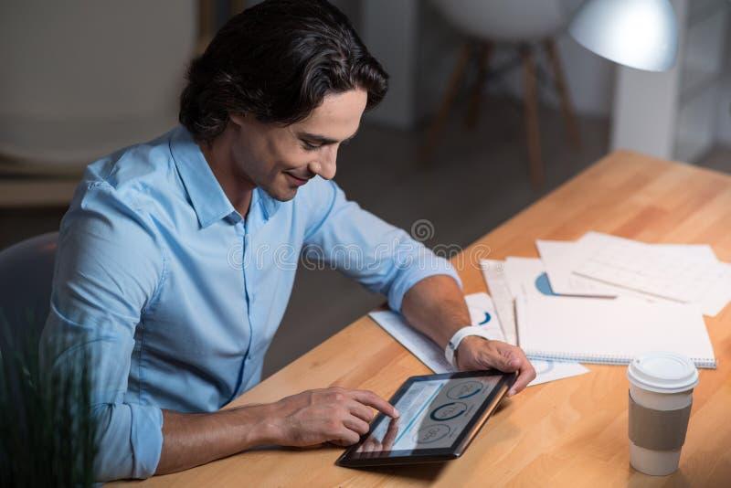 Hombre joven sonriente hermoso que trabaja en la tableta imágenes de archivo libres de regalías