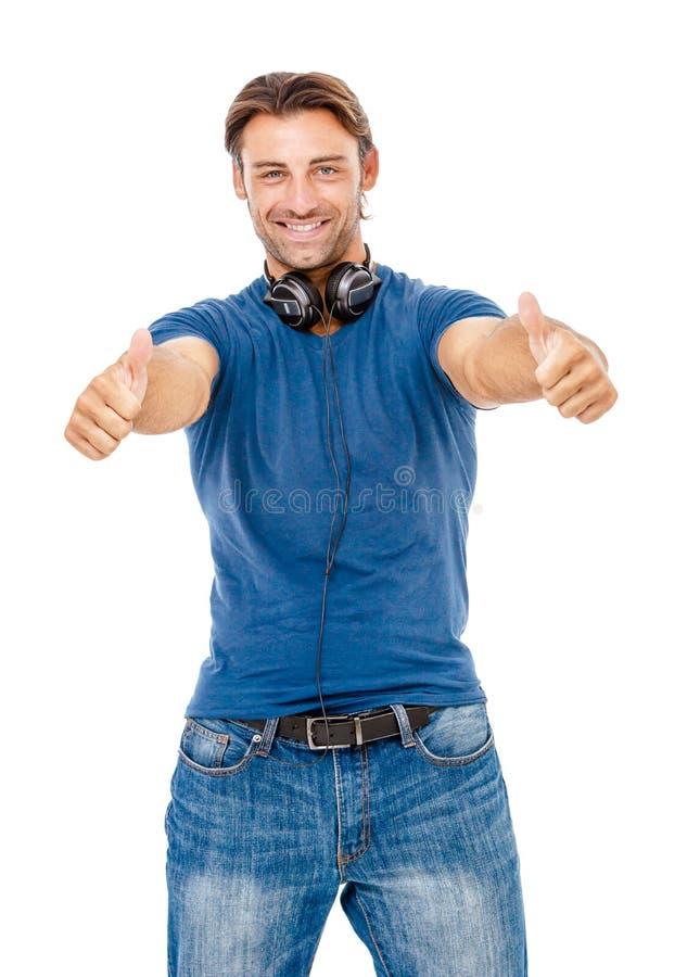 Hombre joven sonriente que le da los pulgares para arriba foto de archivo libre de regalías