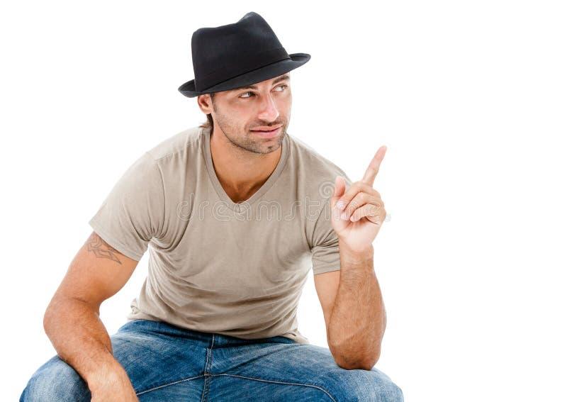 Hombre joven sonriente que señala el espacio de la copia fotografía de archivo libre de regalías