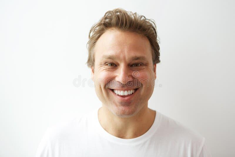 Hombre joven sonriente que se opone a la pared blanca imágenes de archivo libres de regalías
