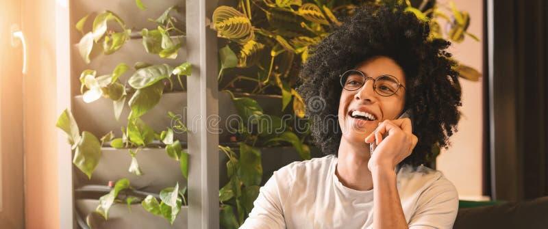 Hombre joven sonriente que se sienta en la cafetería y que habla en el teléfono móvil fotografía de archivo