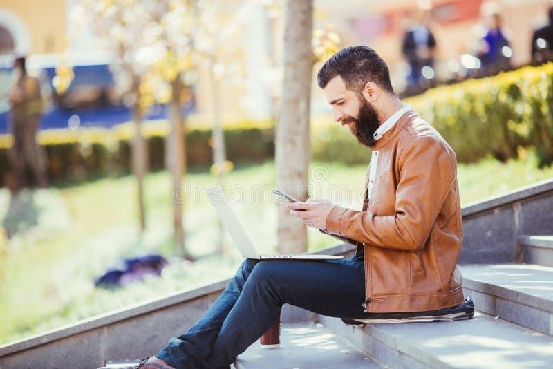 Hombre joven sonriente que se sienta en las escaleras fuera de hablar en el teléfono celular en ciudad fotografía de archivo libre de regalías