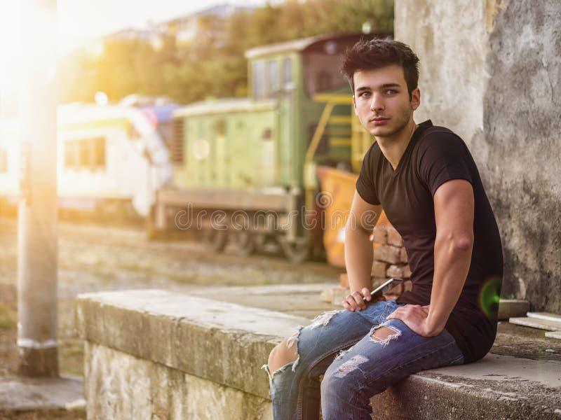 Hombre joven sonriente que se sienta en pasos concretos fotografía de archivo libre de regalías