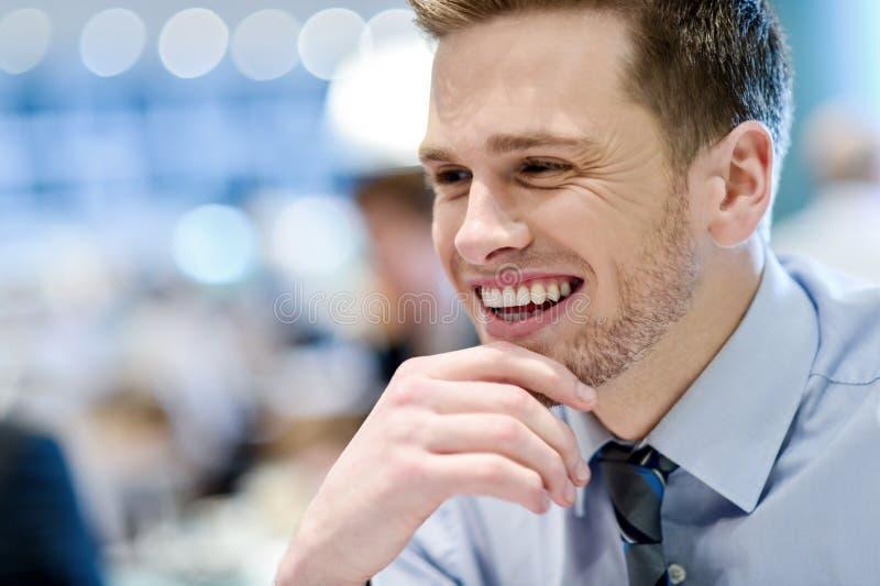 Hombre joven sonriente que se sienta en un café al aire libre imagen de archivo libre de regalías
